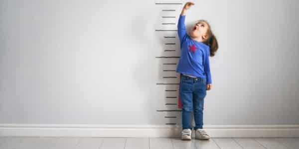 girl next to a height chart representing social media growth