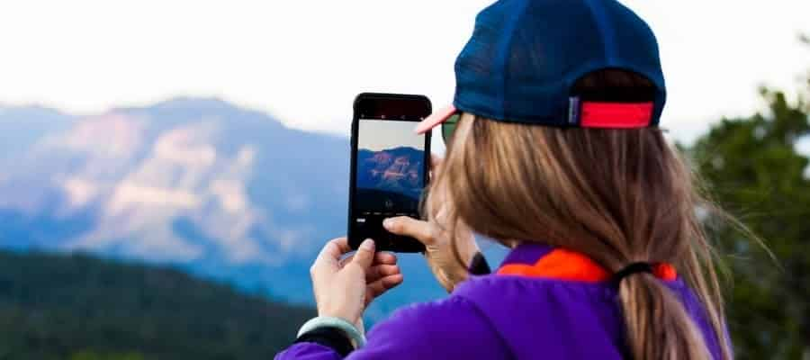 woman taking a social media photo on her cell phone. Looking out over a picturesque mountain range