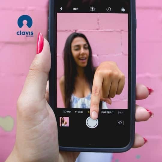 bright pink walled background with a hand holding an iphone in focus. woman jumping out of the screen to press a button on the phone